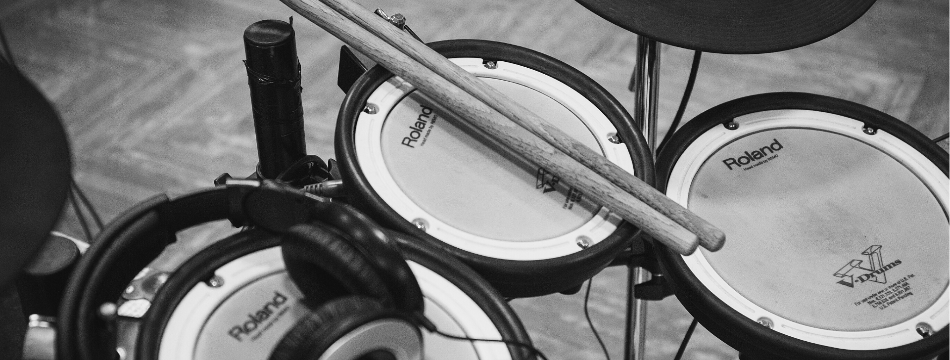 learning to drum at home: electronic drum kit with drumsticks resting on the tom