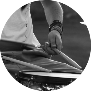 person holding drumsticks over a snare drum